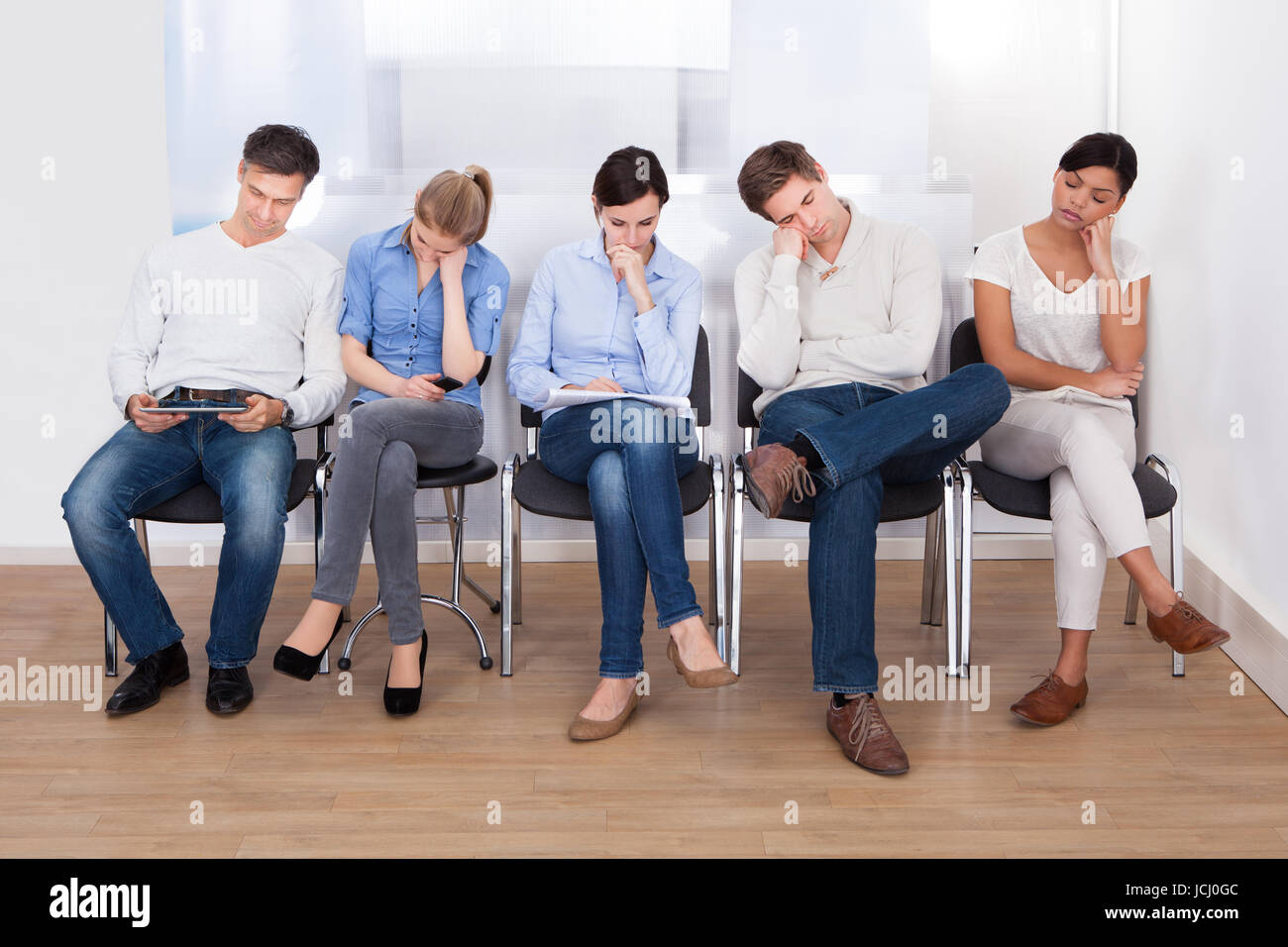 young group of people sleeping on chair in a waiting room stock