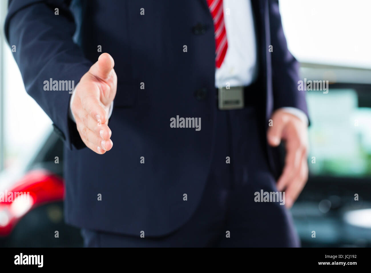 Seller or car salesman in car dealership presenting his new and used cars in the showroom - Stock Image