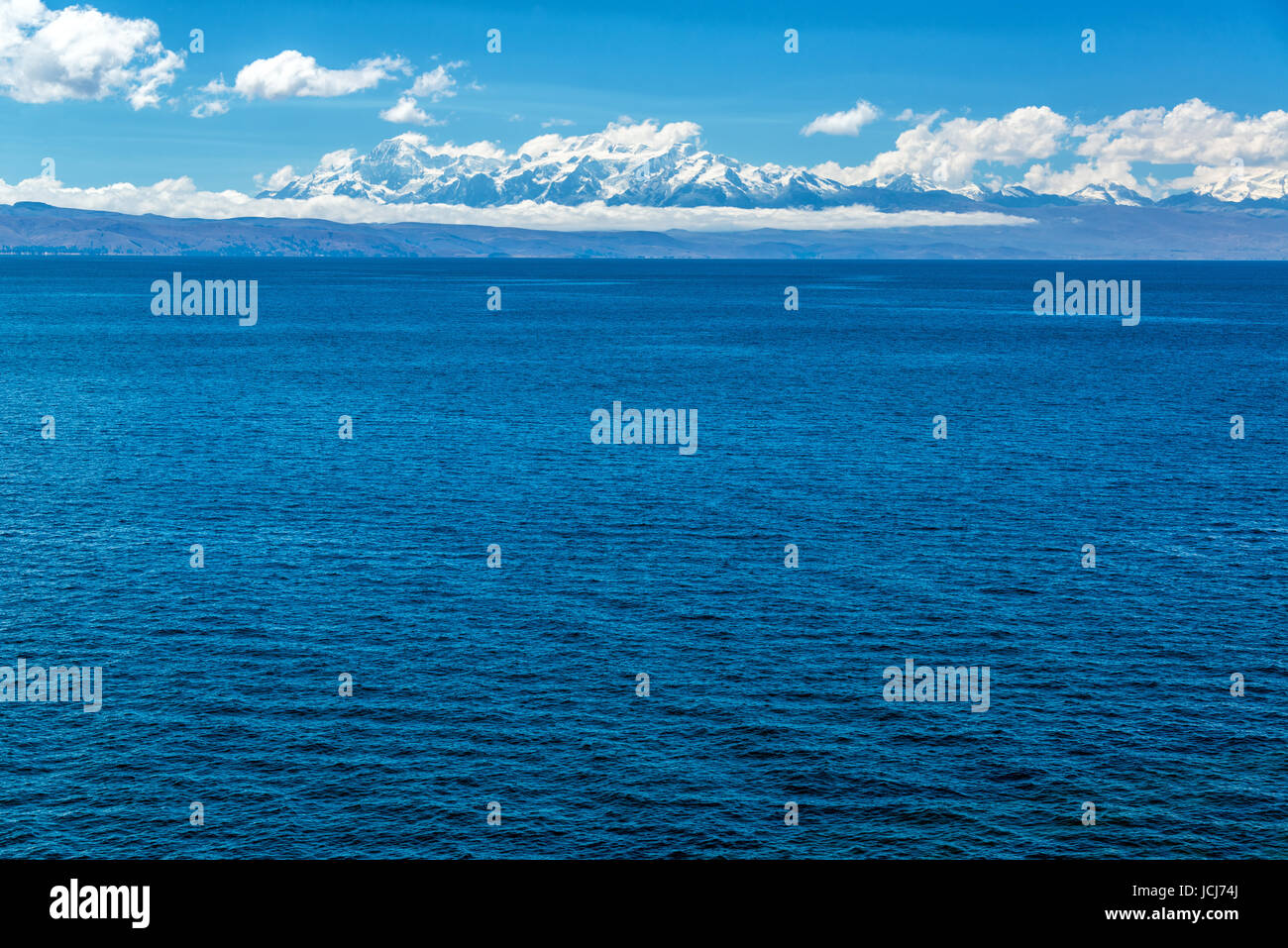 View of the Andes mountains with the deep blue of Lake Titicaca in the foreground - Stock Image