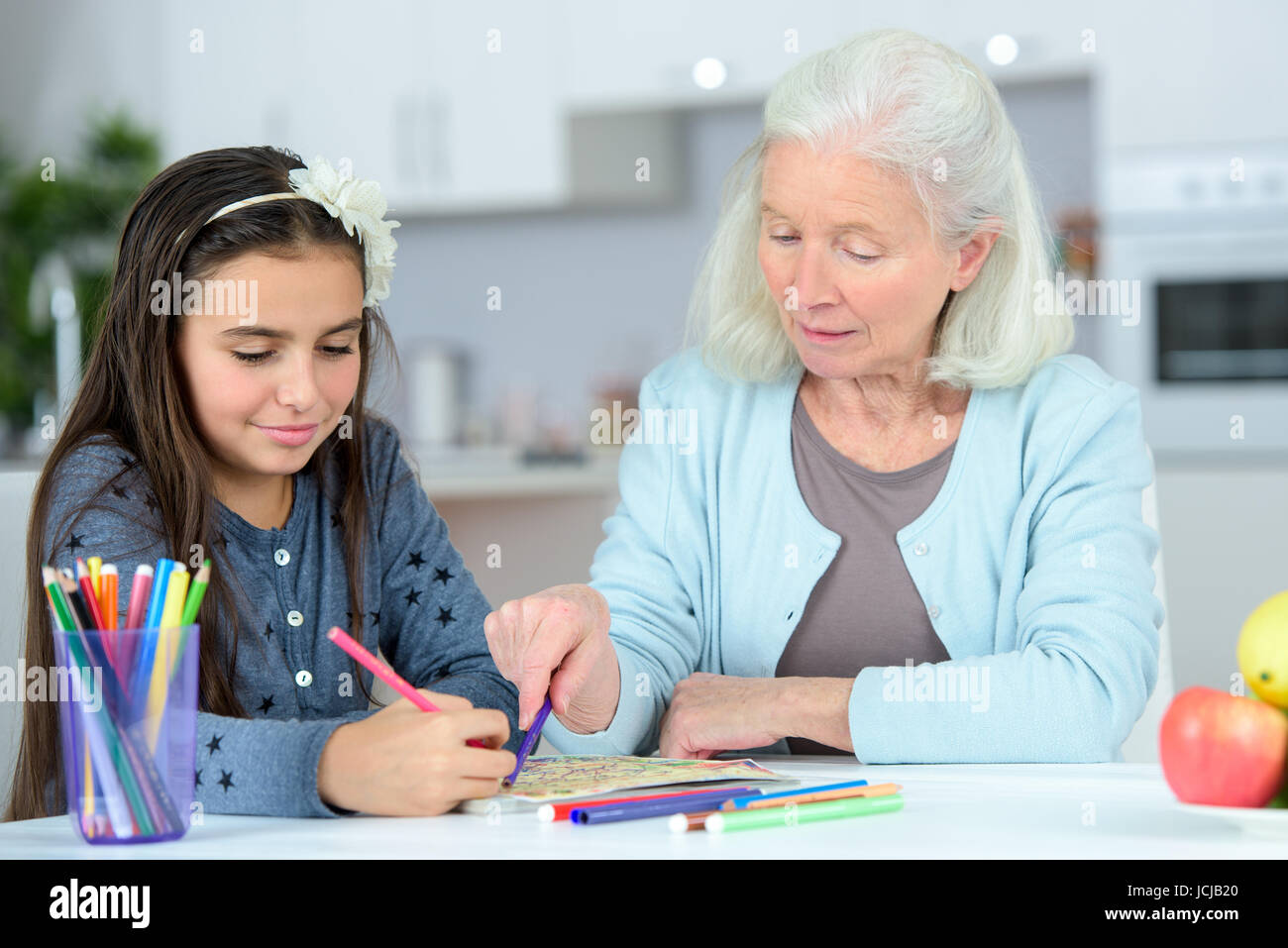 portrait of little girl with grandmother drawing with pencils - Stock Image