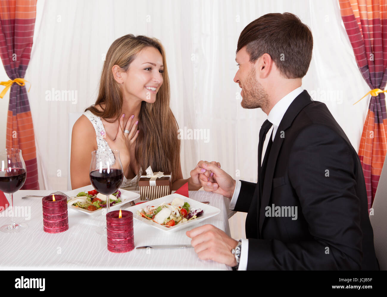a09d710ffc84 Happy young woman receives a gift from her partner. Romantic dinner setting  with young couple dressed in evening wear