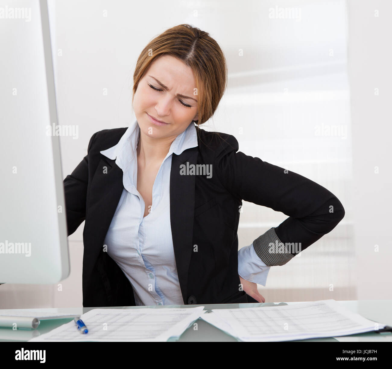 Business Woman With Back Pain Holding Her Aching Hip - Stock Image