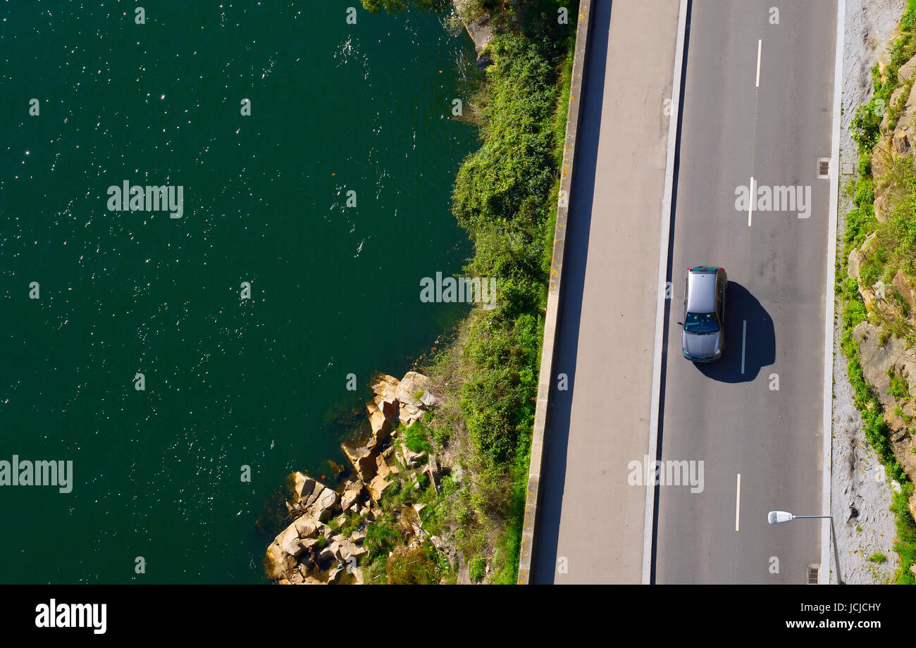 Car going on a road near the river, aerial view. - Stock Image