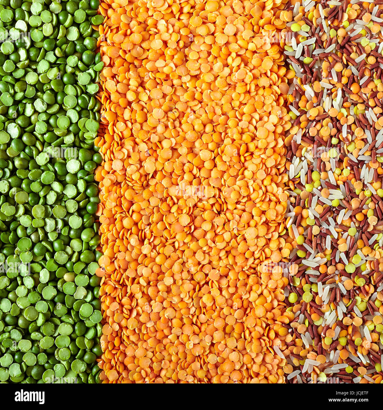 Vertical layers of dried legumes, from left to right: green split peas, red lentils and mix of red Thai rice, white Stock Photo