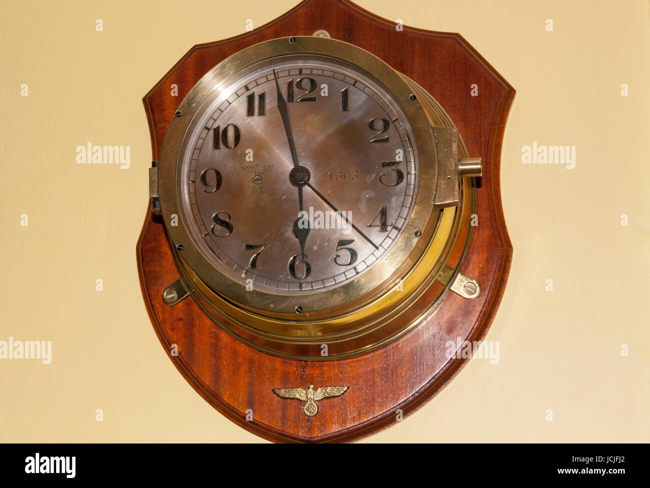A working genuine U-Boat clock from U1303 mounted on a wooden base and displayed on wall - Stock Image