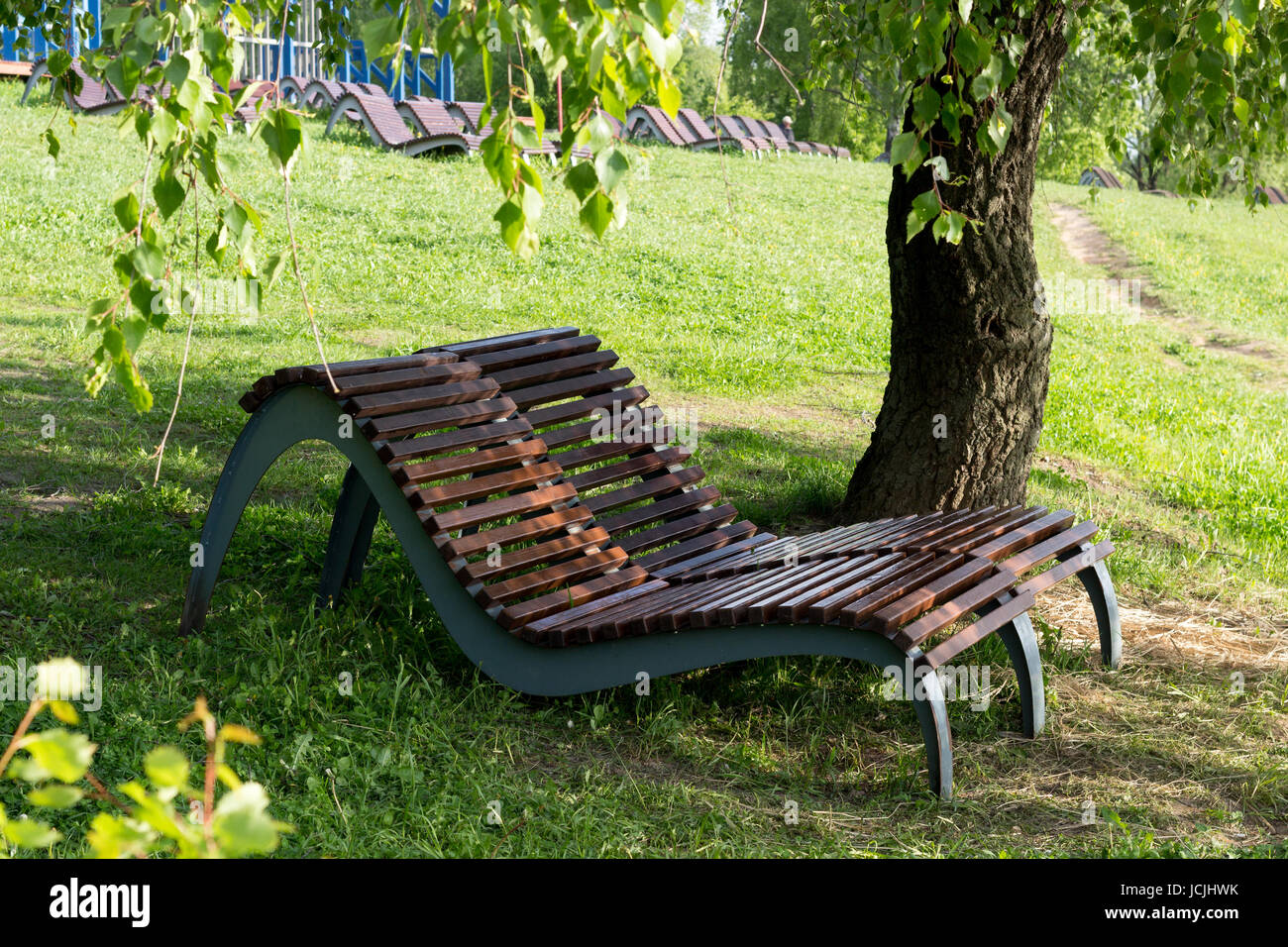 Recreation area in the park, wooden chaise lounges under a shady tree in a park on the river bank - Stock Image
