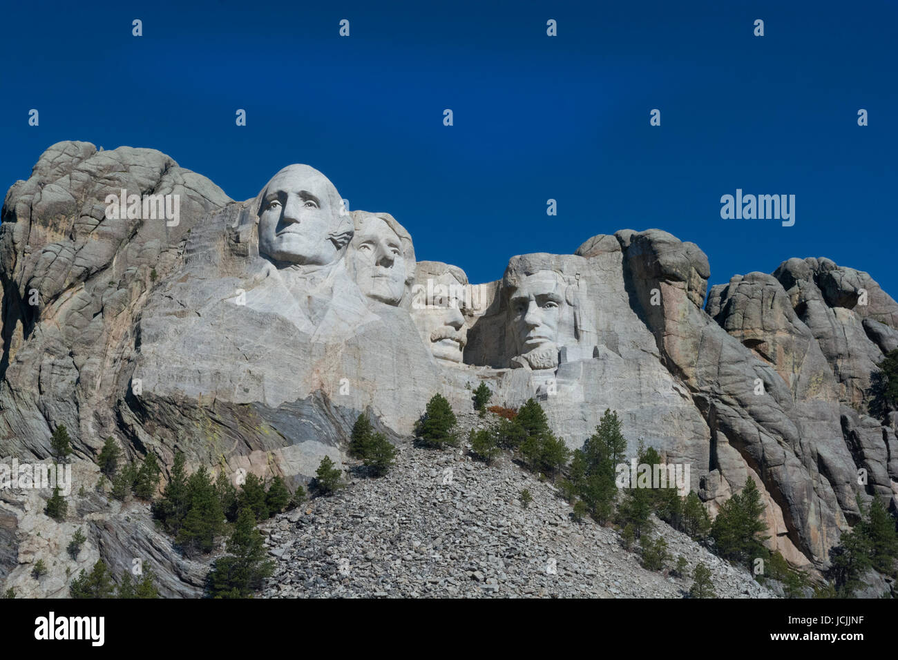 Mount Rushmore set against a bright cloud free blue sky. Stock Photo
