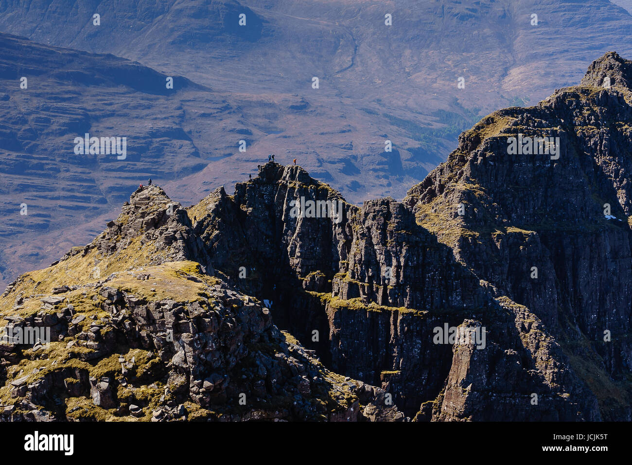 Walkers Scrambling Across the Na Rathanen Pinnacles on Liathach - Stock Image