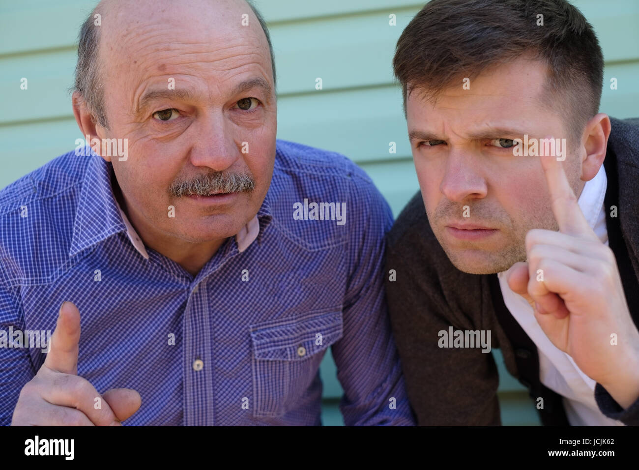 Satisfied men showing index finger up, giving advice or recommendation - Stock Image