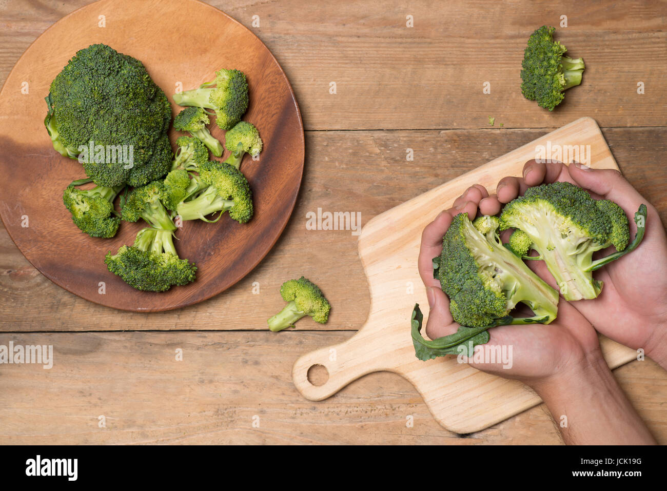Top view of Chef hand cutting broccoli for cooking - Stock Image