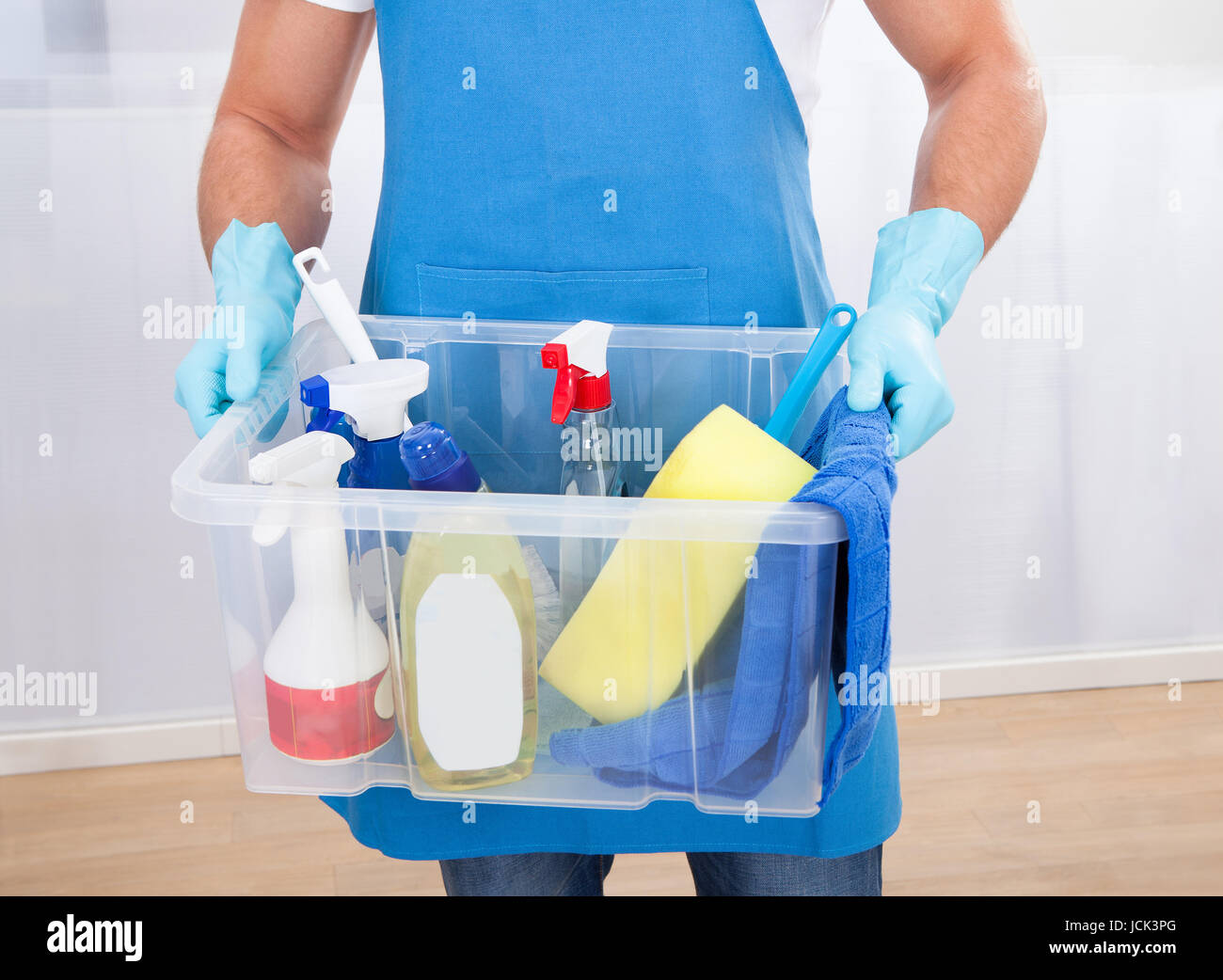 Janitor or cleaner wearing an apron and gloves carrying a tub of ...