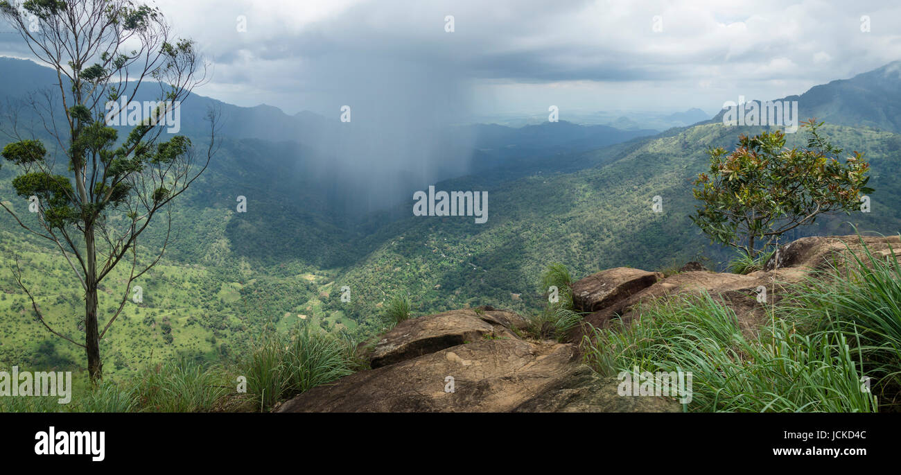 massive raincloud in the green valley, view from Ella Rock with stones and trees - Stock Image