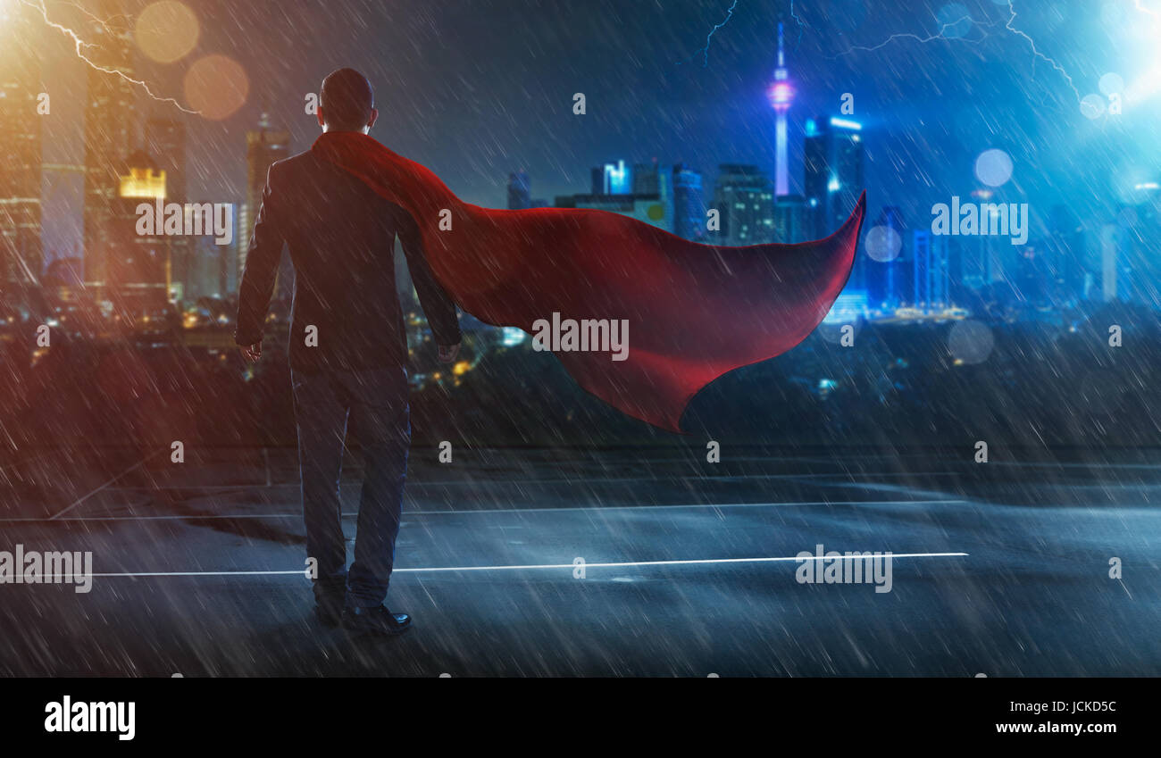 Businessman in a suit and cape hero facing a storm,victory concept. cityscape background , night scene . - Stock Image