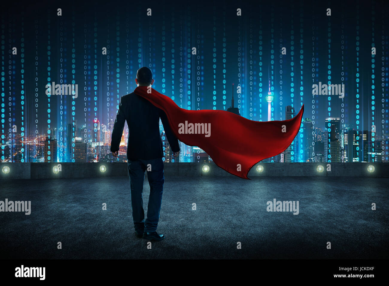 Businessman in a suit and cape hero standing on rooftop with virtual modern city skyline . - Stock Image
