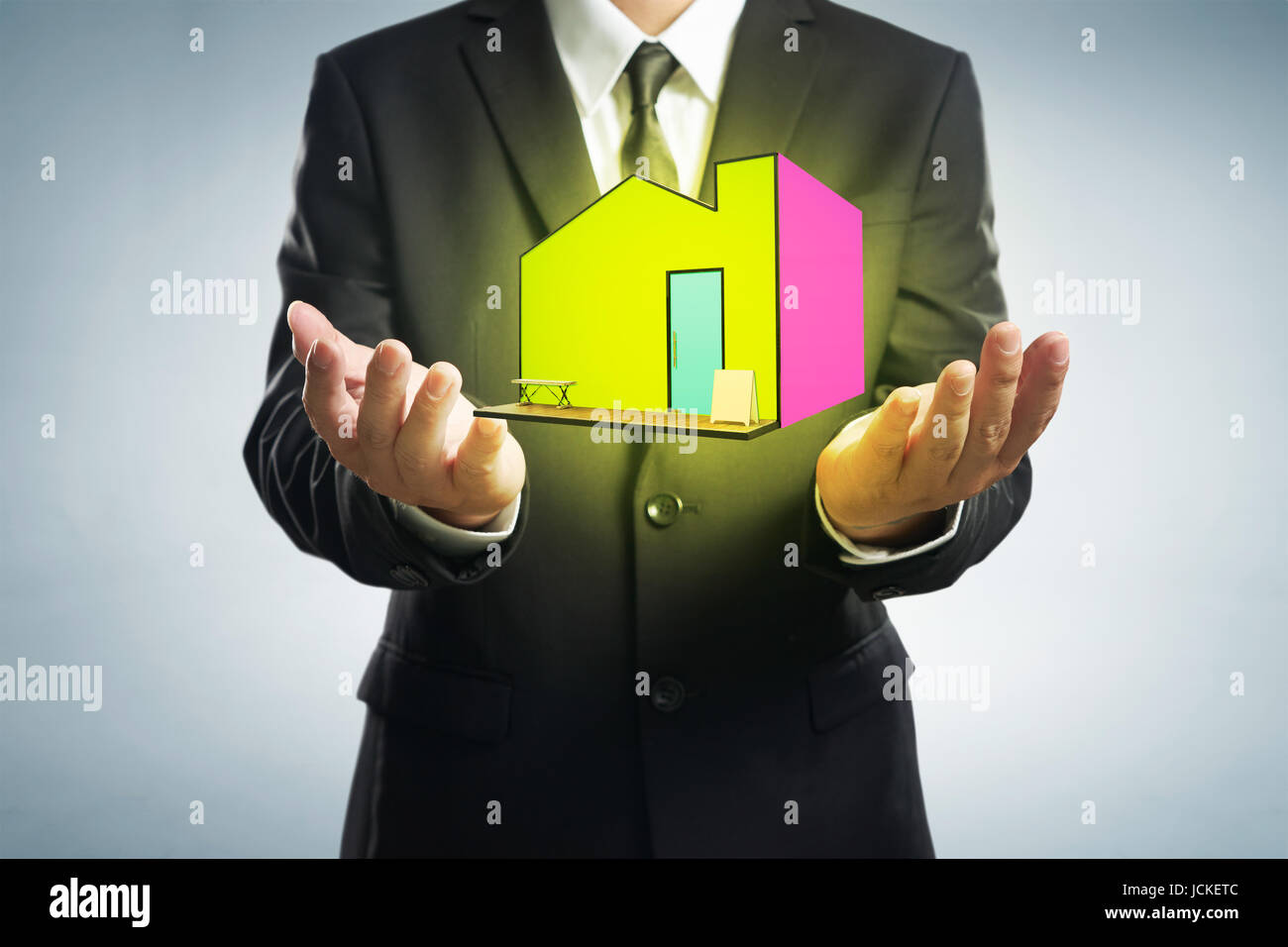 Dreams house concepts. Businessman with give gesture and icon of home with grey background. - Stock Image