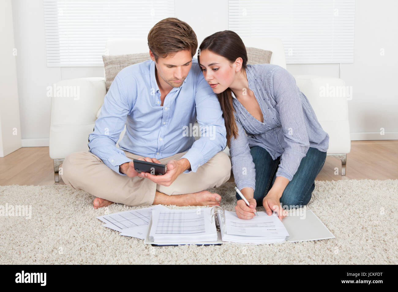 Superior Full Length Of Couple Calculating Budget In Living Room At Home