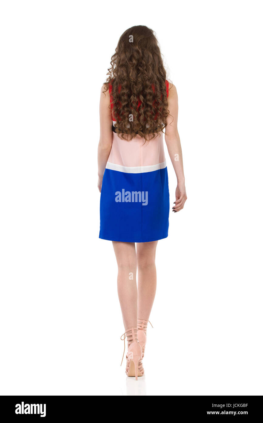 Young woman in colorful mini dress and high heels is walking. Rear view. Full length studio shot isolated on white. - Stock Image