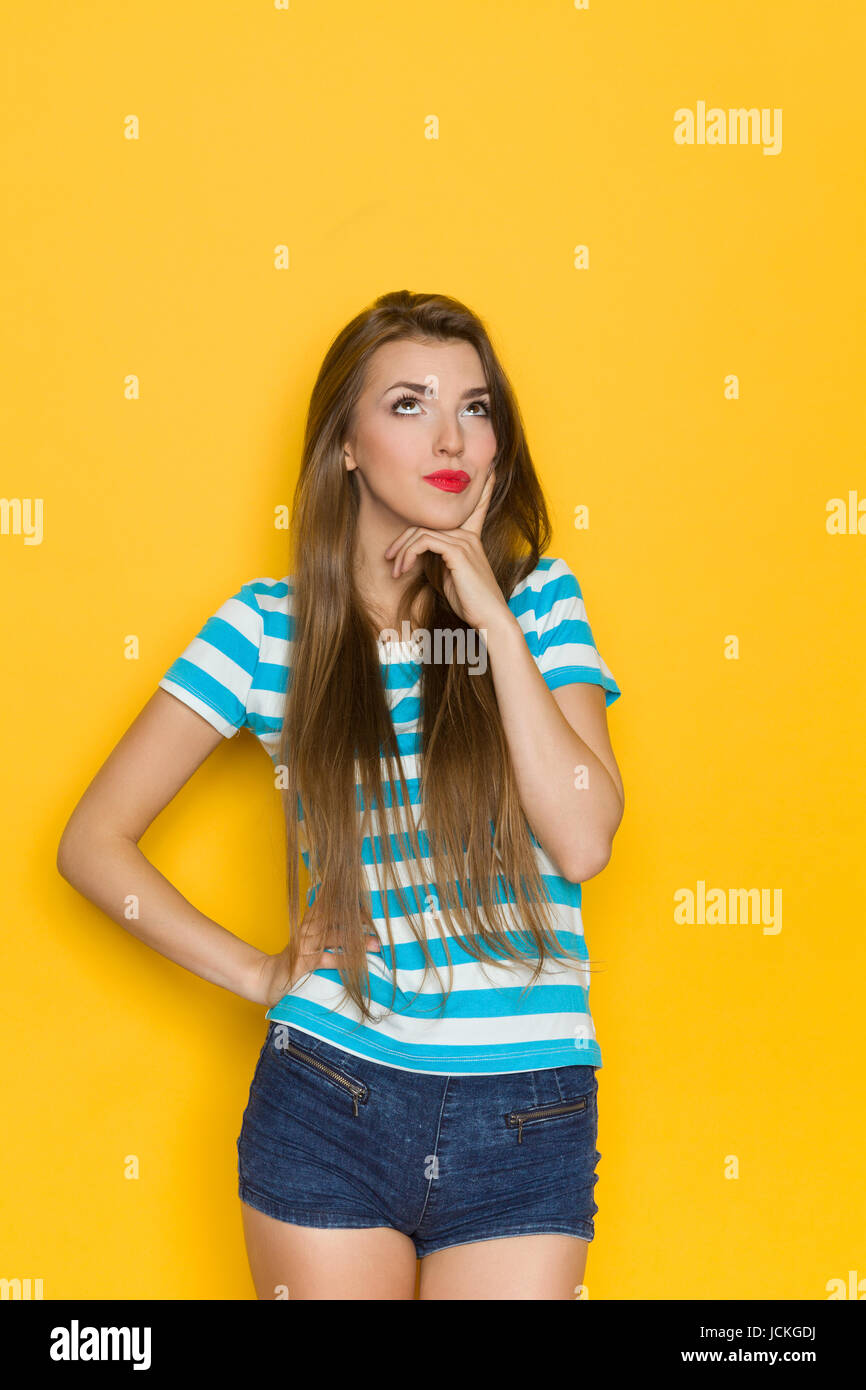 Young woman in blue striped shirt and jeans shorts holding hand on chin, grimacing and looking up. Three quarter - Stock Image