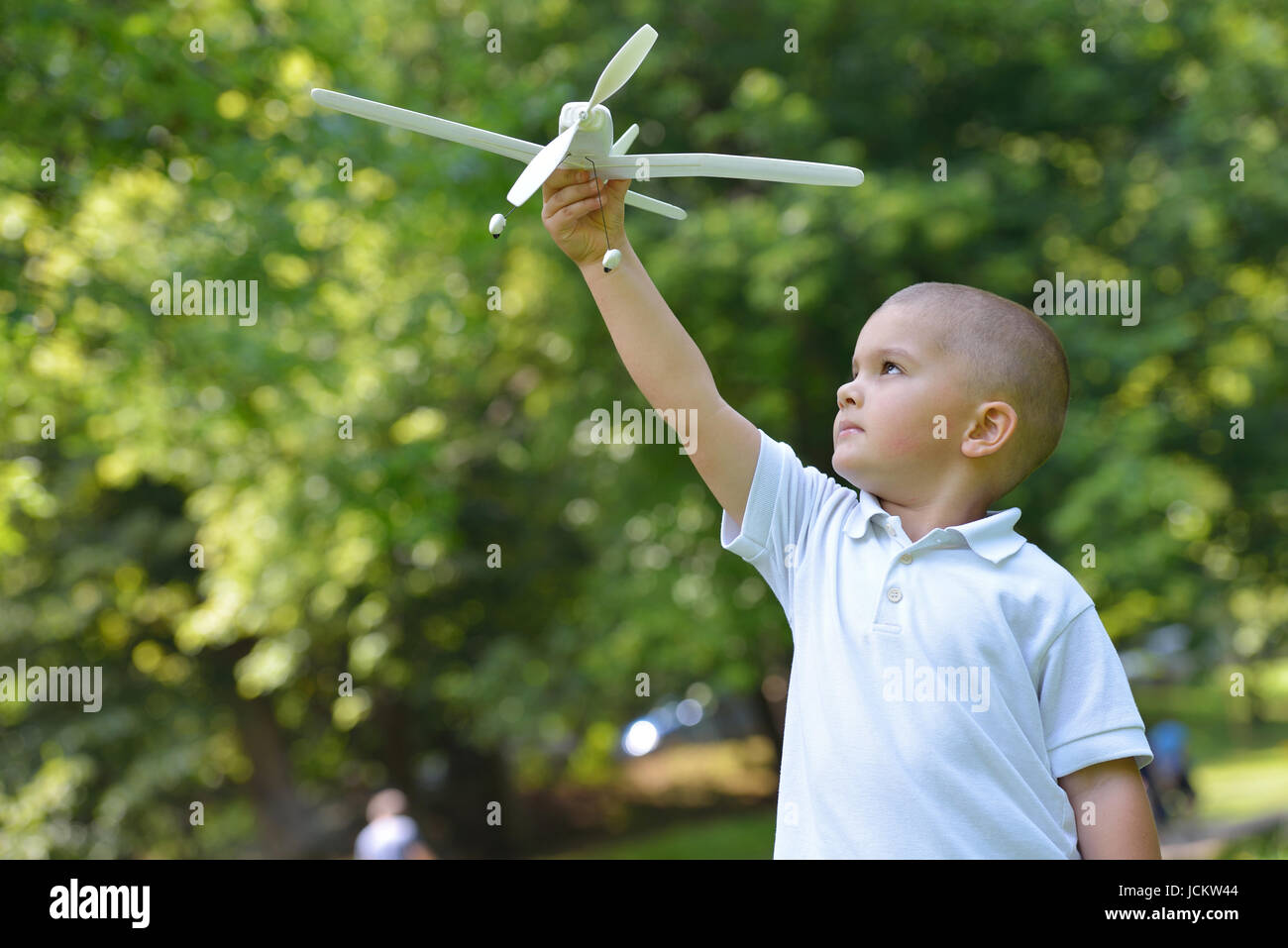 happy boy play and  throw airplane in park - Stock Image