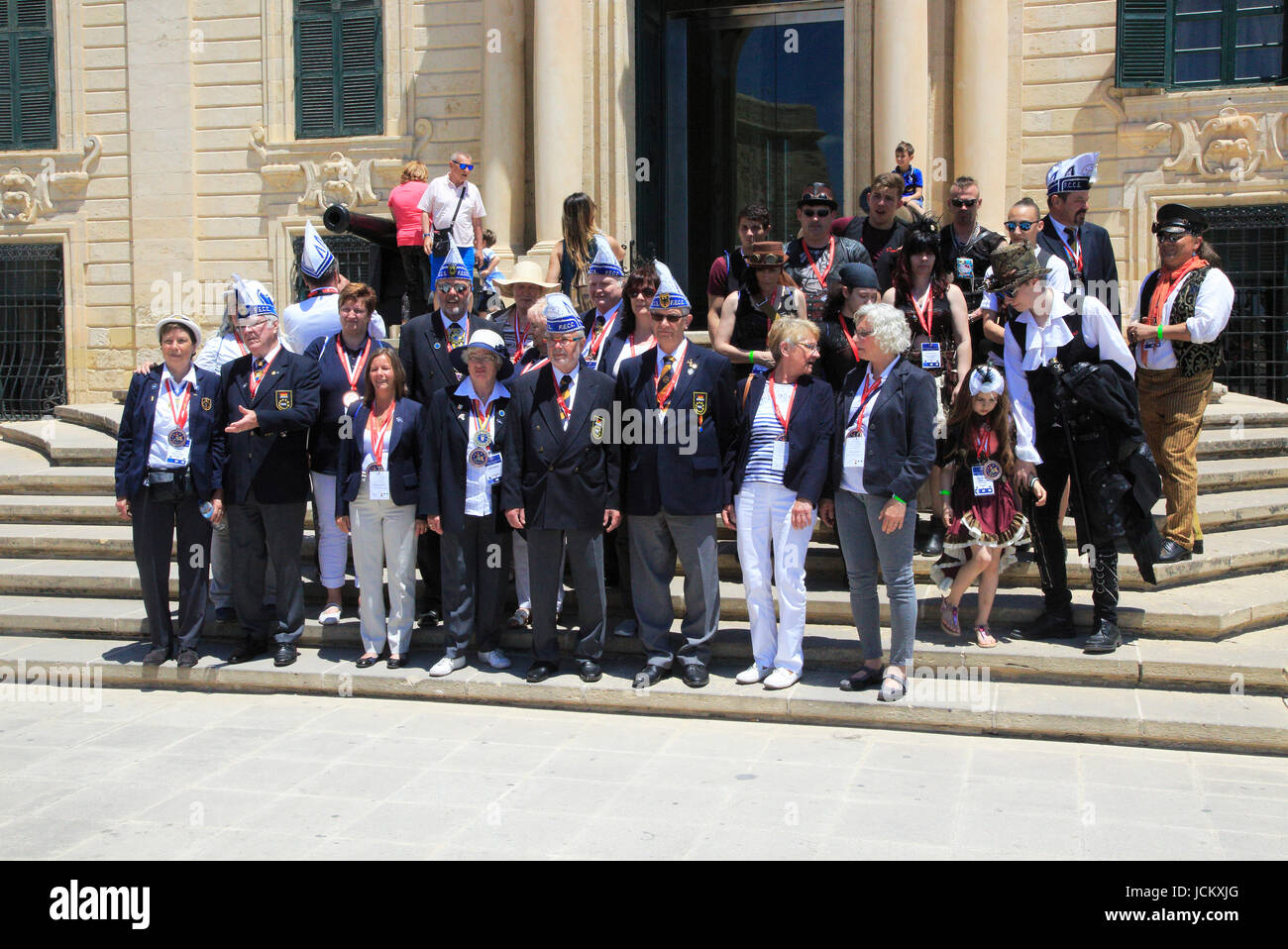Tour group photo of carnival organisers on steps of Auberge de Castille palace in city centre of Valletta, Malta Stock Photo