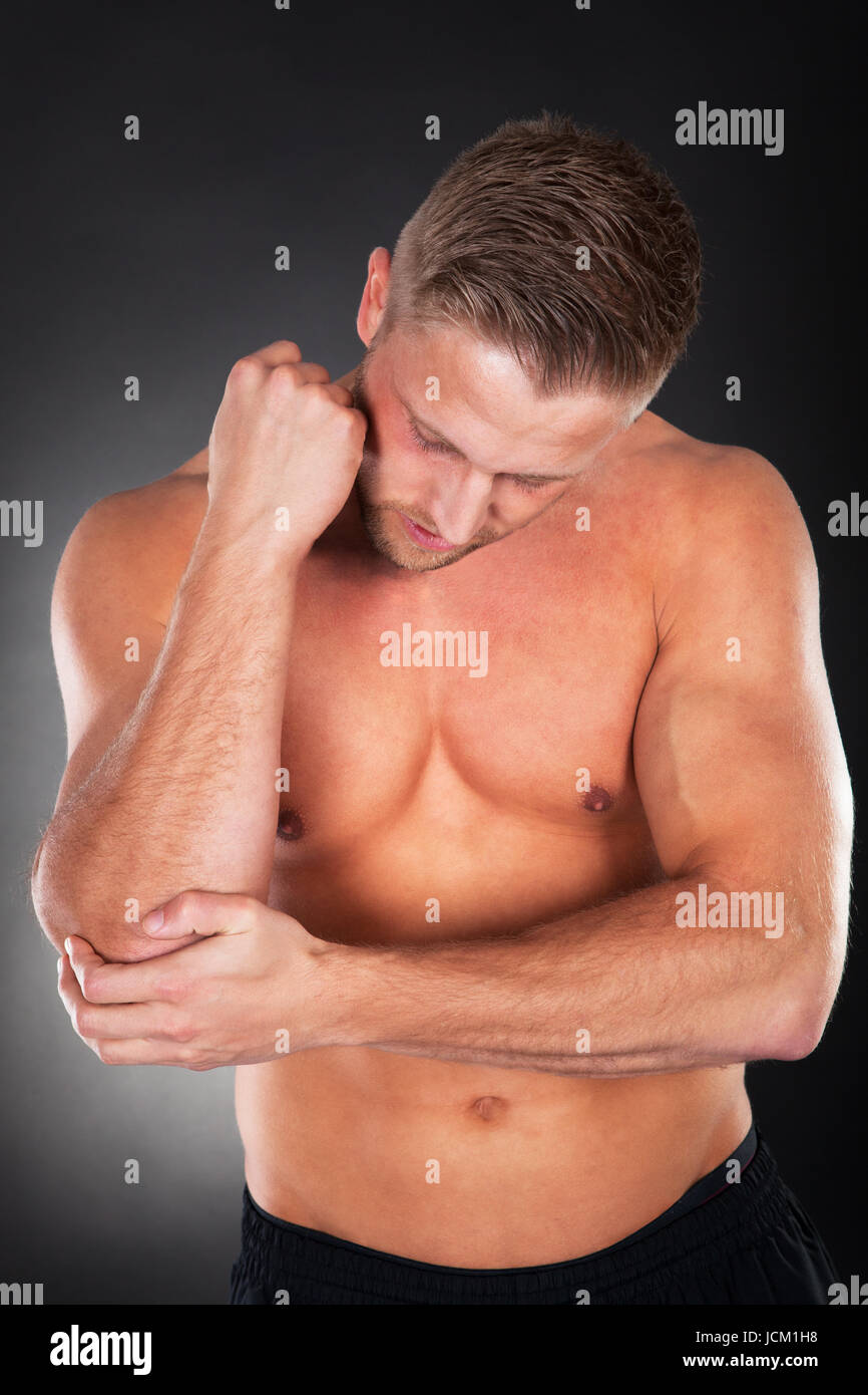 Fit muscular young man with an elbow injury standing shirtless looking down as he massages it with his other hand - Stock Image