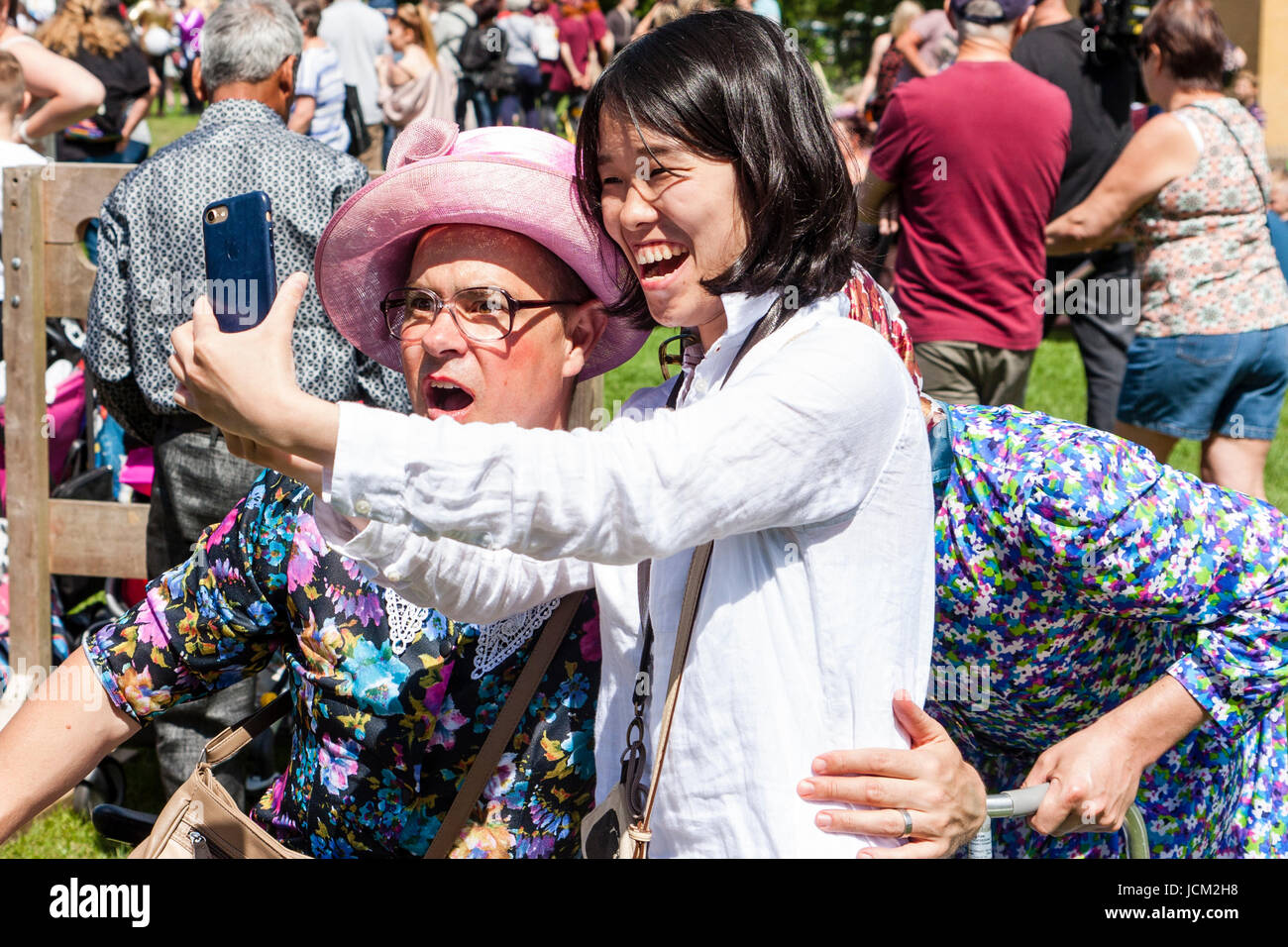 England, Coxheath. World custard pie championships. Laughing Japanese girl taking selfie with one of the Grannie's - Stock Image