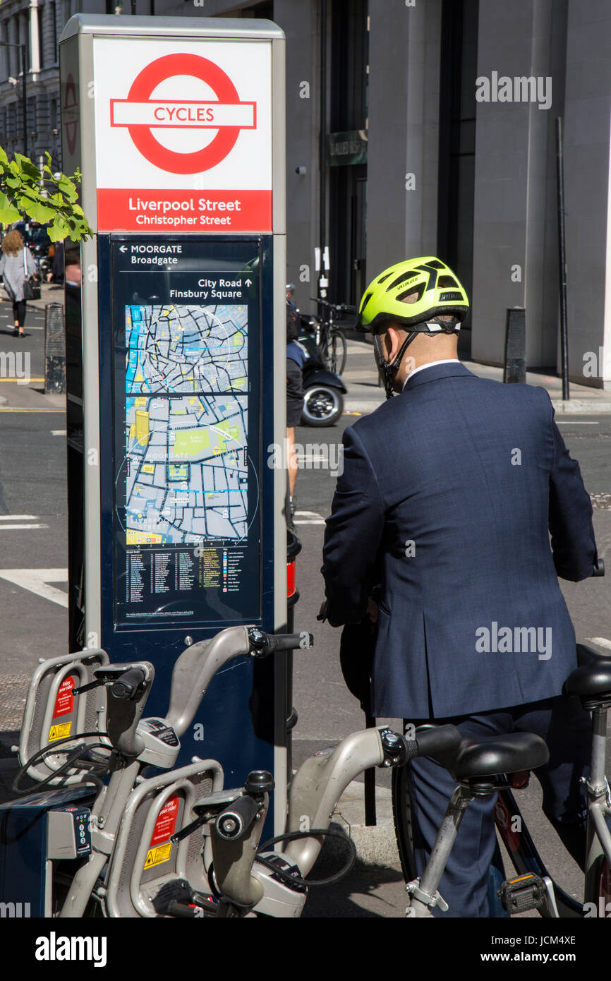 Business man in a suit, wearing a cycle helmet and riding a bicycle, looking at a cycle map of central London. - Stock Image