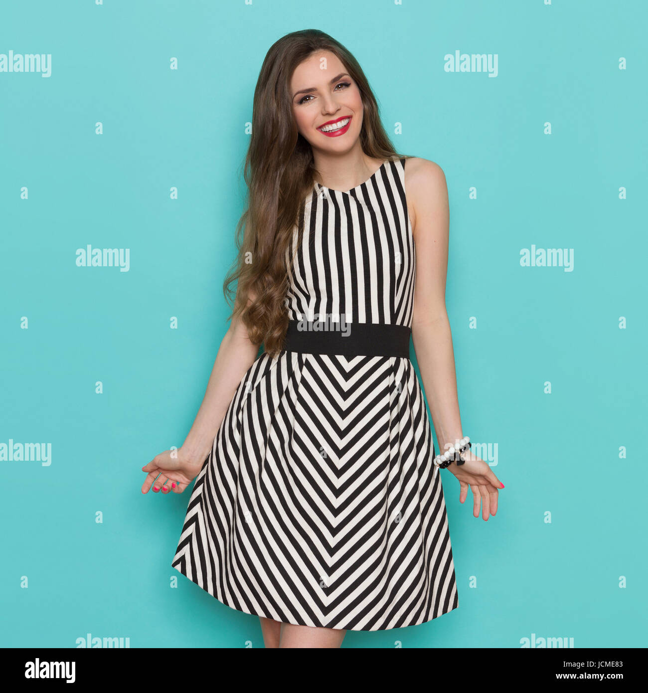 a7e19a4e56f Beautiful girl in black and white striped dress posing smiling and looking  at camera