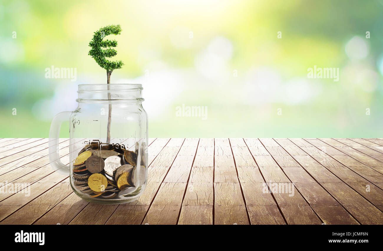 Coins in the glass with Euro shape plant growing ,savings,growing,investment,retirement and education concept . - Stock Image