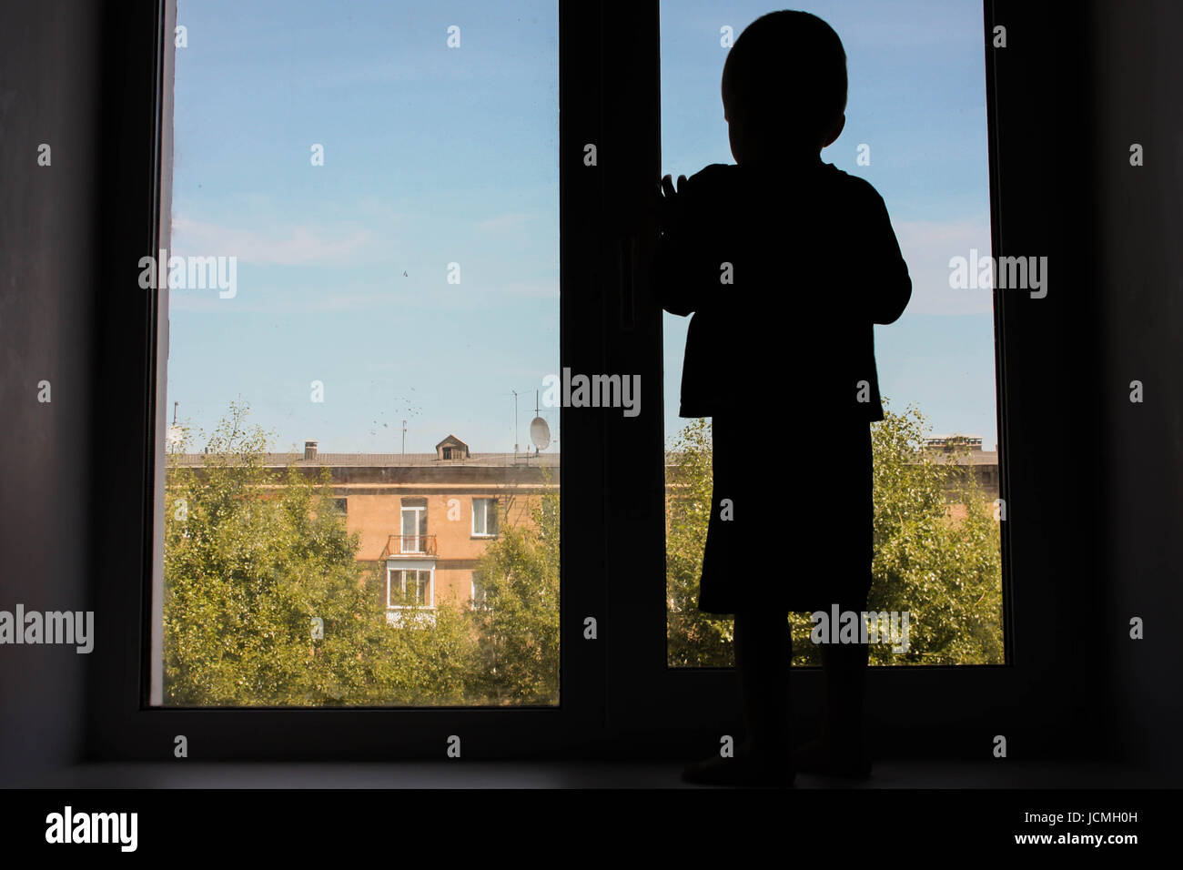 Child deviant behavior concept. The child looks out the window. Photo for your design. The child looks out the window. - Stock Image
