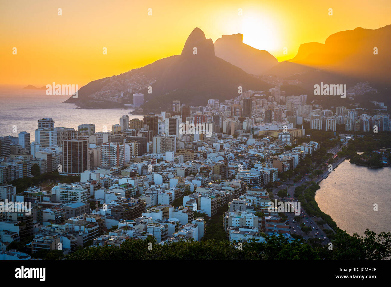 A dramatic skyline view of sunset over Ipanema with Two Brothers Mountain looking over both the Atlantic Ocean and - Stock Image