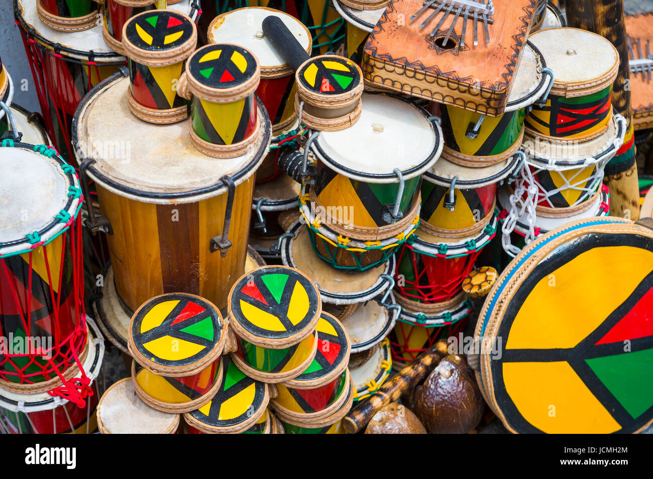 Afro-Brazilian drums and musical instruments stacked up in historic tourist district of Pelourinho, Salvador, Brazil. - Stock Image