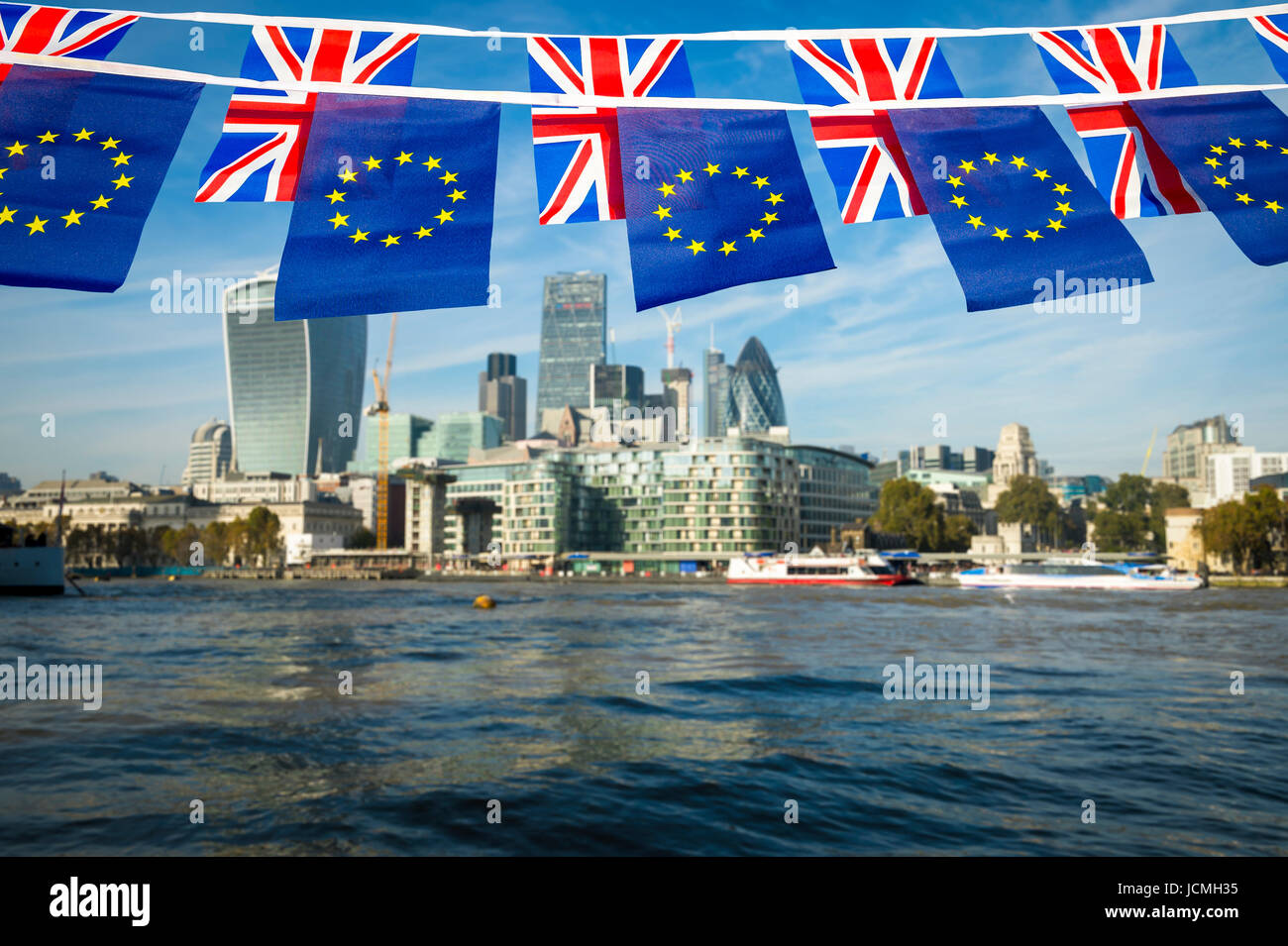 European Union and Union Jack bunting flags flying over the London skyline of the financial City center at the River - Stock Image