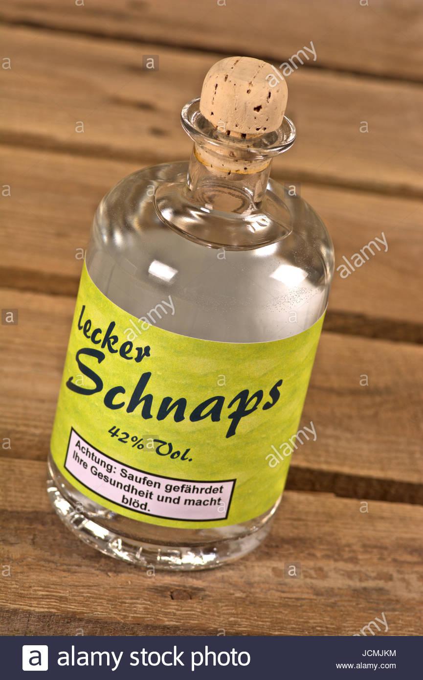 Lecker Schnaps - Flasche mit Etikett und klarem Alkohol - (Korn oder Wodka) - auf rustikalem Holzboden mit Warnhinweis. Stock Photo