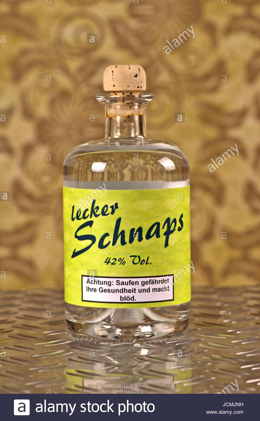 Lecker Schnaps - Flasche mit Etikett und klarem Alkohol - (Korn oder Wodka) - auf Riffelblech vor alter Mustertapete Stock Photo