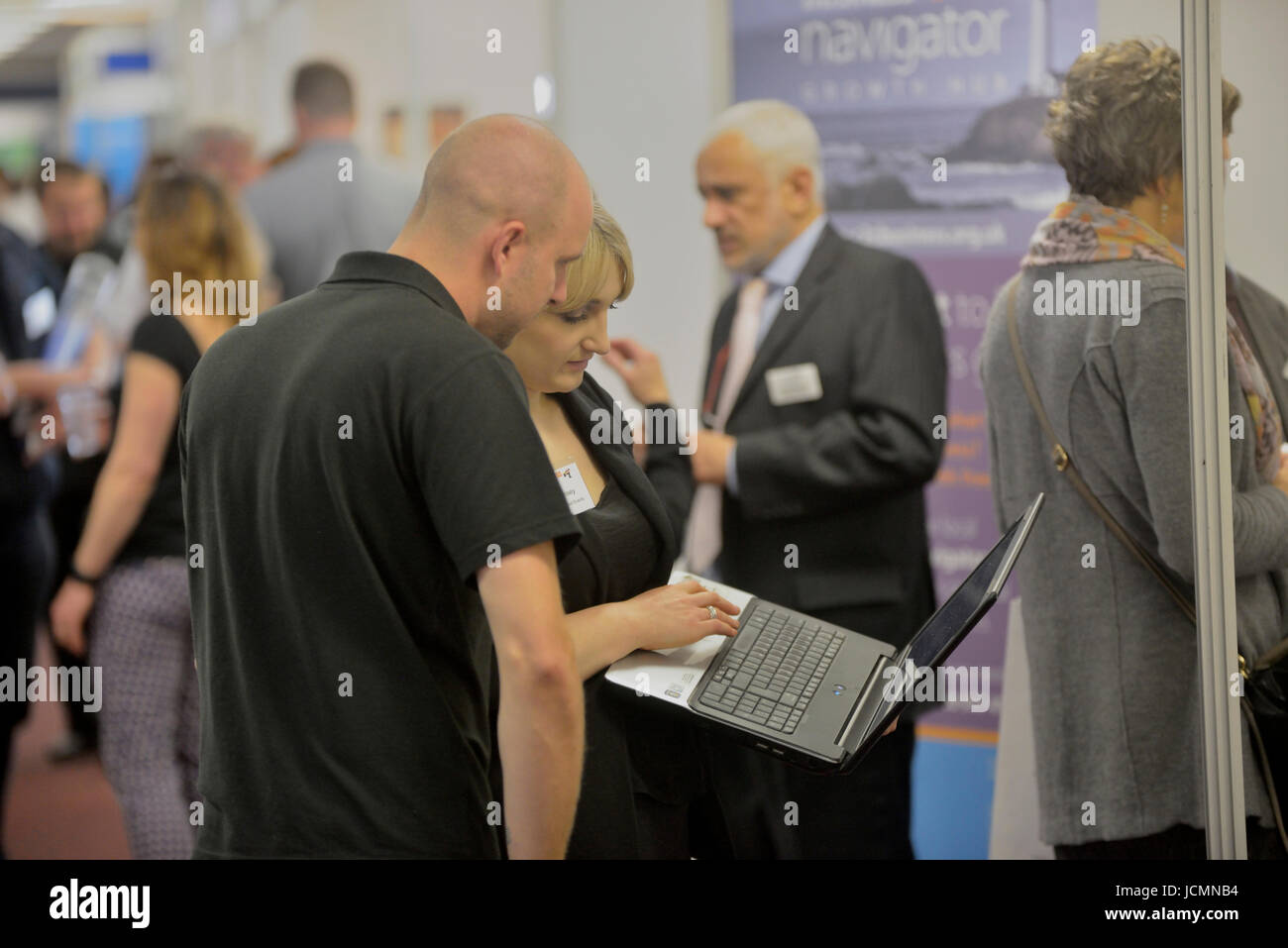 Business people using a laptop at a business conference. England. UK - Stock Image