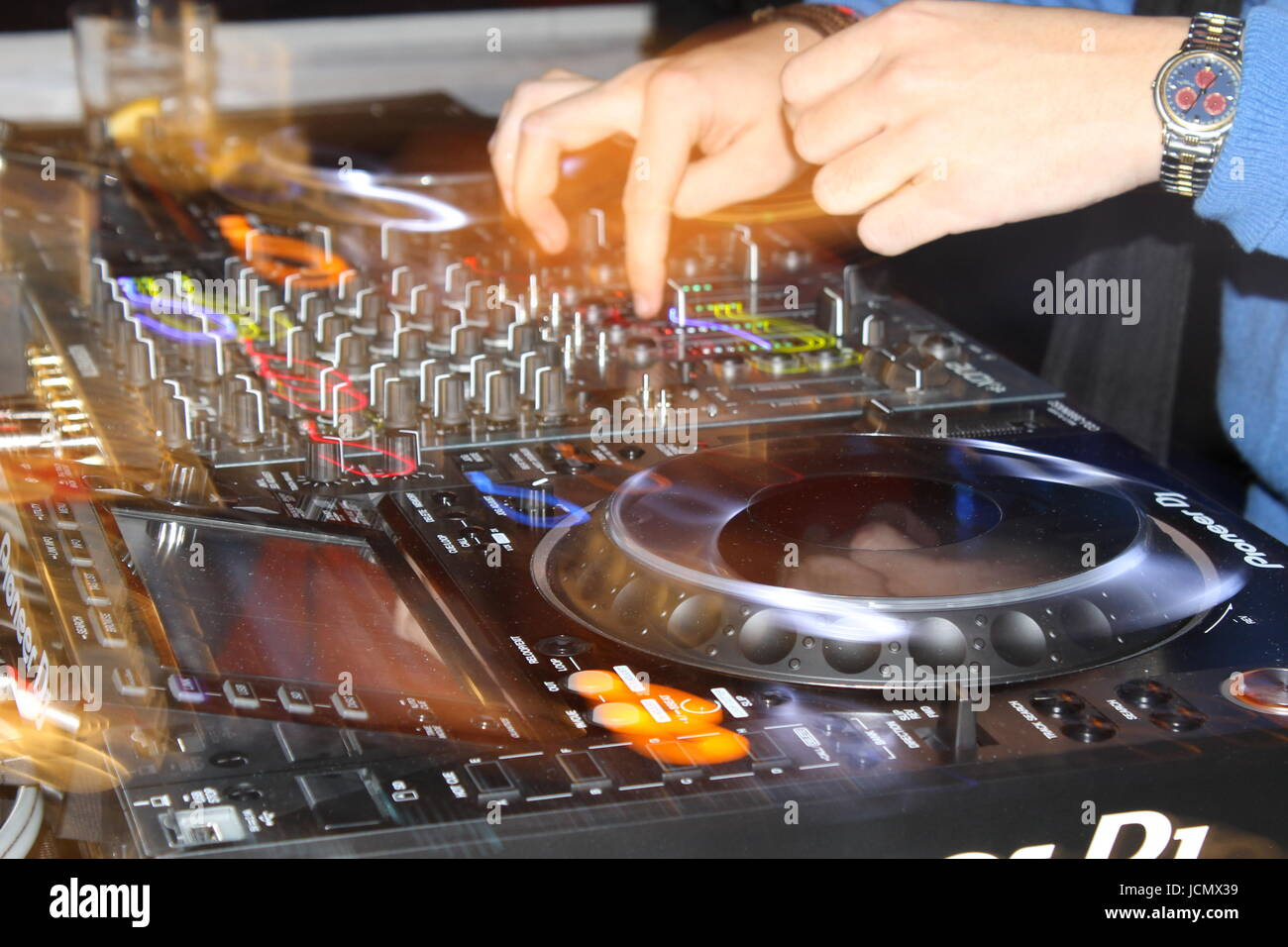Close up of a DJ playing with CDJs and a mixer - Stock Image