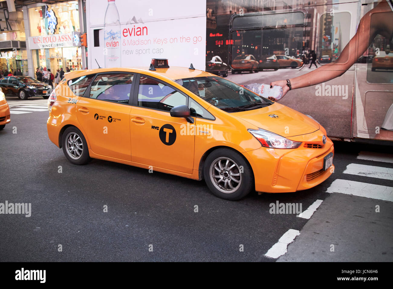 toyota prius V yellow cab in the evening in Times Square New York City USA - Stock Image
