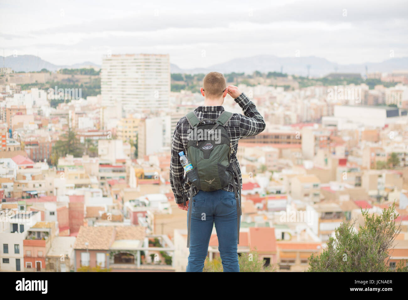 Traveller looks out over view of the city. Alicante in Spain - Stock Image