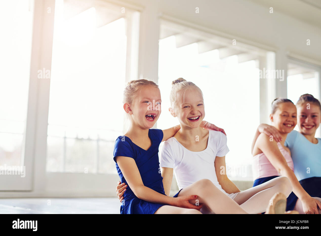 Cute little girls embracing and laughing sitting on floor in ballet class together. - Stock Image