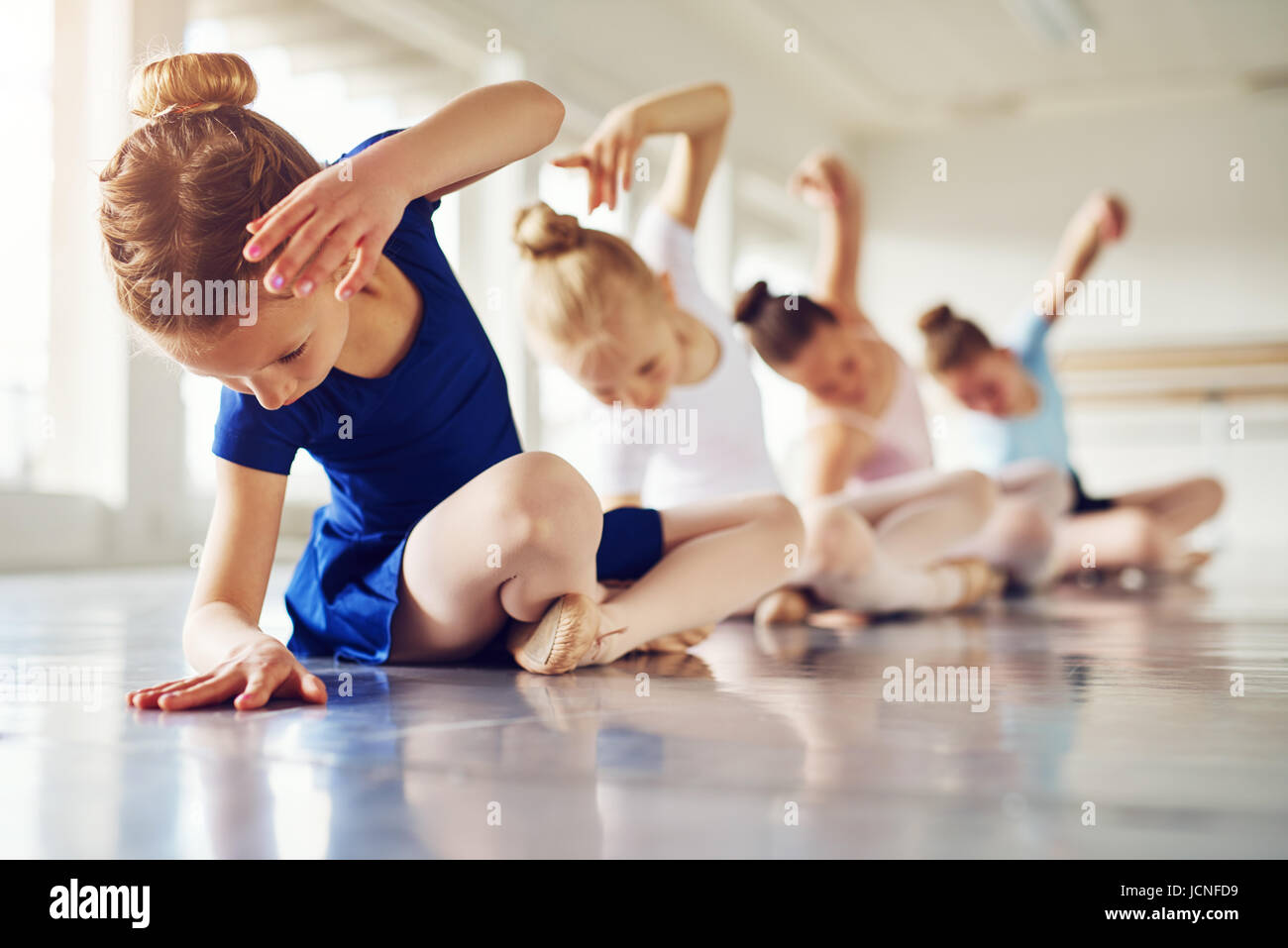 Little ballerinas doing exercises and bending sitting on floor in ballet class. - Stock Image