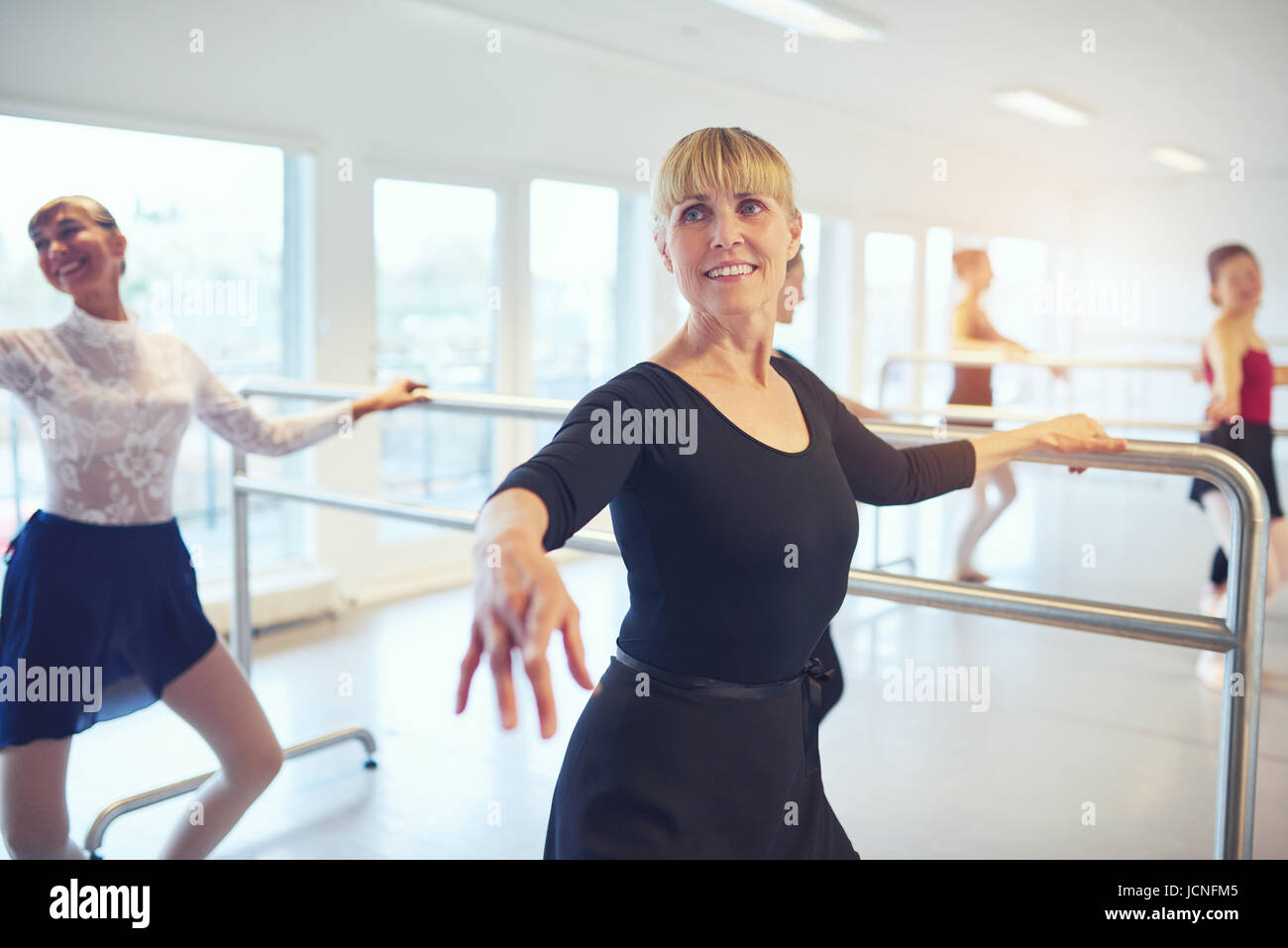 Smiling adult ballerinas standing and doing exercises in ballet class. - Stock Image