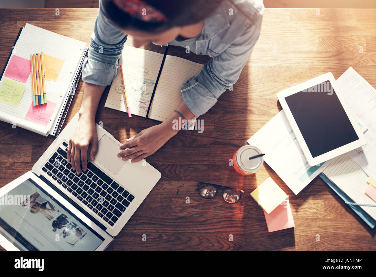 From above young entrepreneur woman sitting and typing a laptop at the workplace in office. - Stock Image