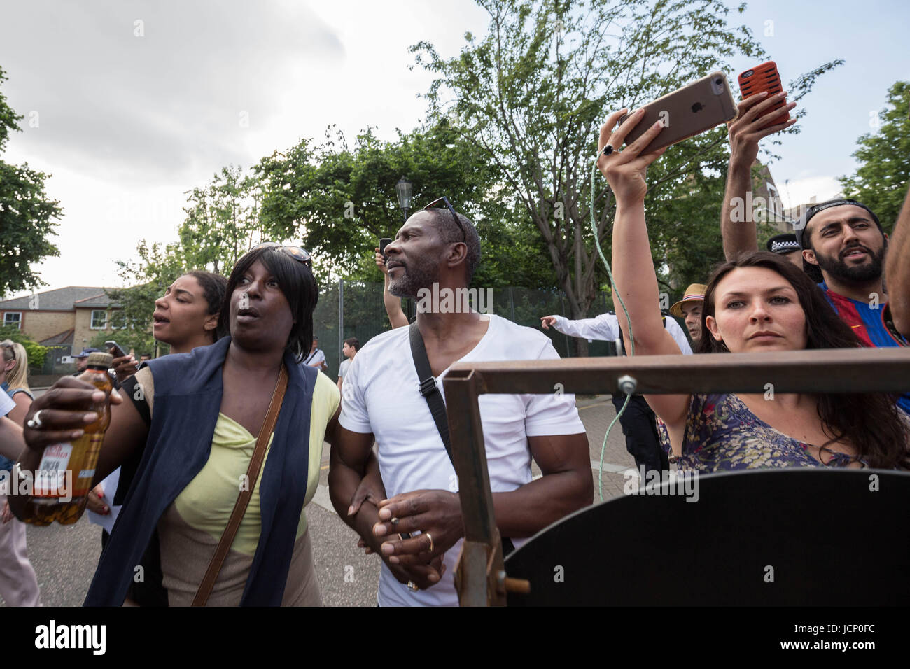 London, UK. 16th June, 2017. Angry scuffles with locals and police as PM Theresa May leaves St Clement's Church - Stock Image