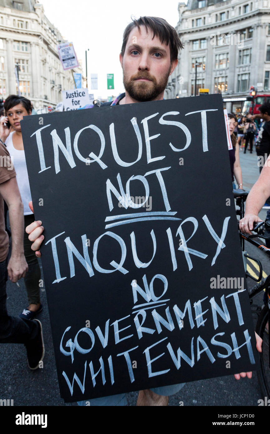 London, UK, 16 June 2017. A protester holds an 'Inquest not Inquiry' posterat the Justice for Grenfell Protest - Stock Image
