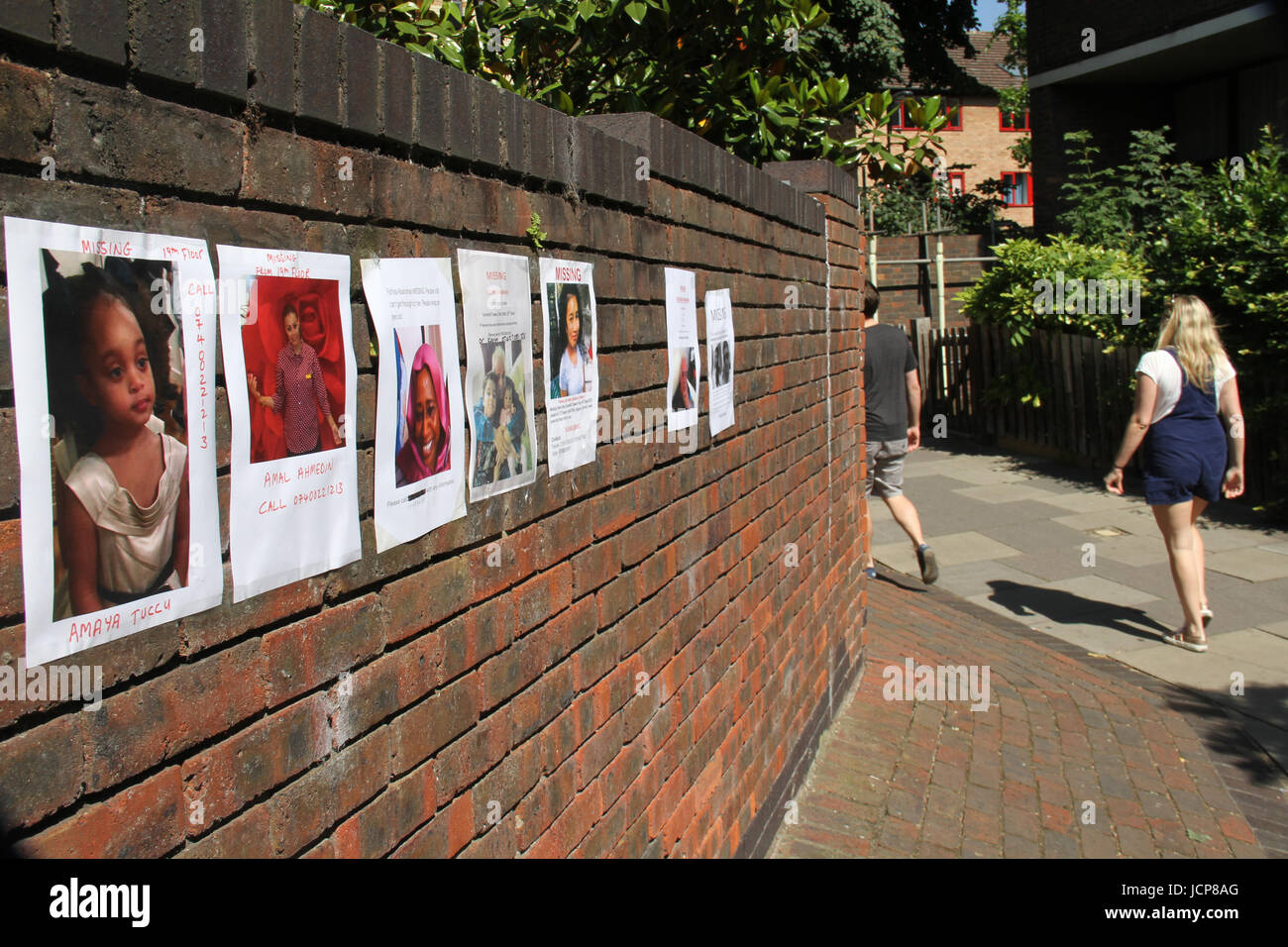 London, UK. 16th June, 2017. People walk past a wall with postered with some of the missing Grenfell Tower residence. - Stock Image