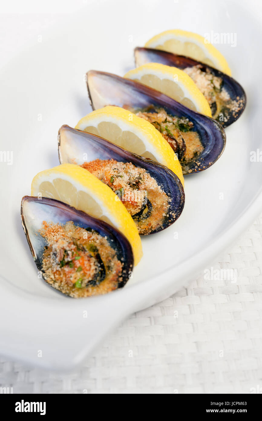 Grilled mussels cooked in the oven, accompanied by slices of lemon, grated pan and parsley. Mussels cooked on white Stock Photo