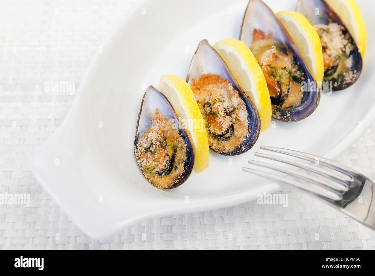 Grilled mussels cooked in the oven, accompanied by slices of lemon, grated pan and parsley. Mussels cooked on white - Stock Image