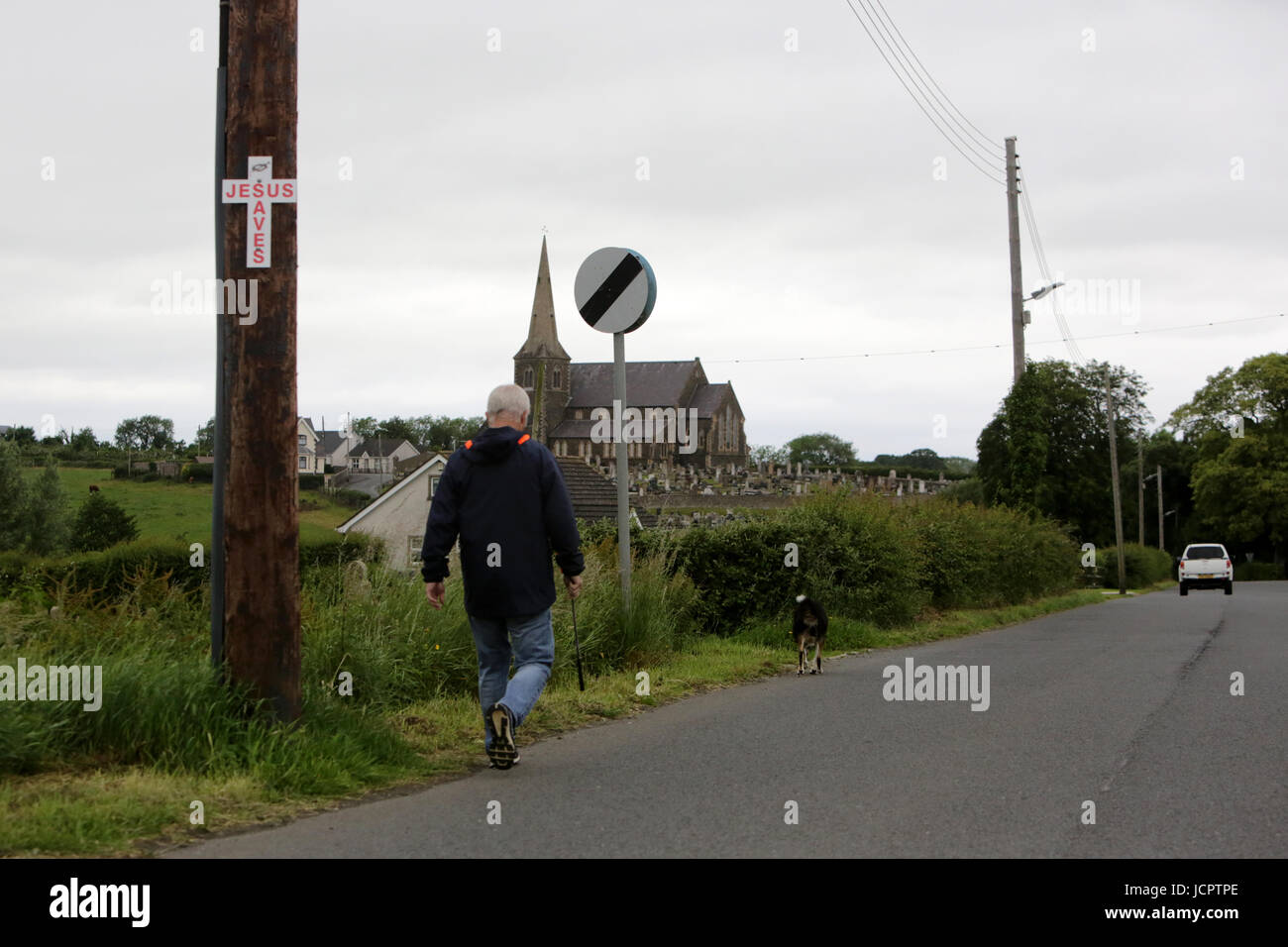A man walks his dog down the Derryanvil Road close to Drumcree Church, Portadown 20 years since the Drumcree standoff Stock Photo