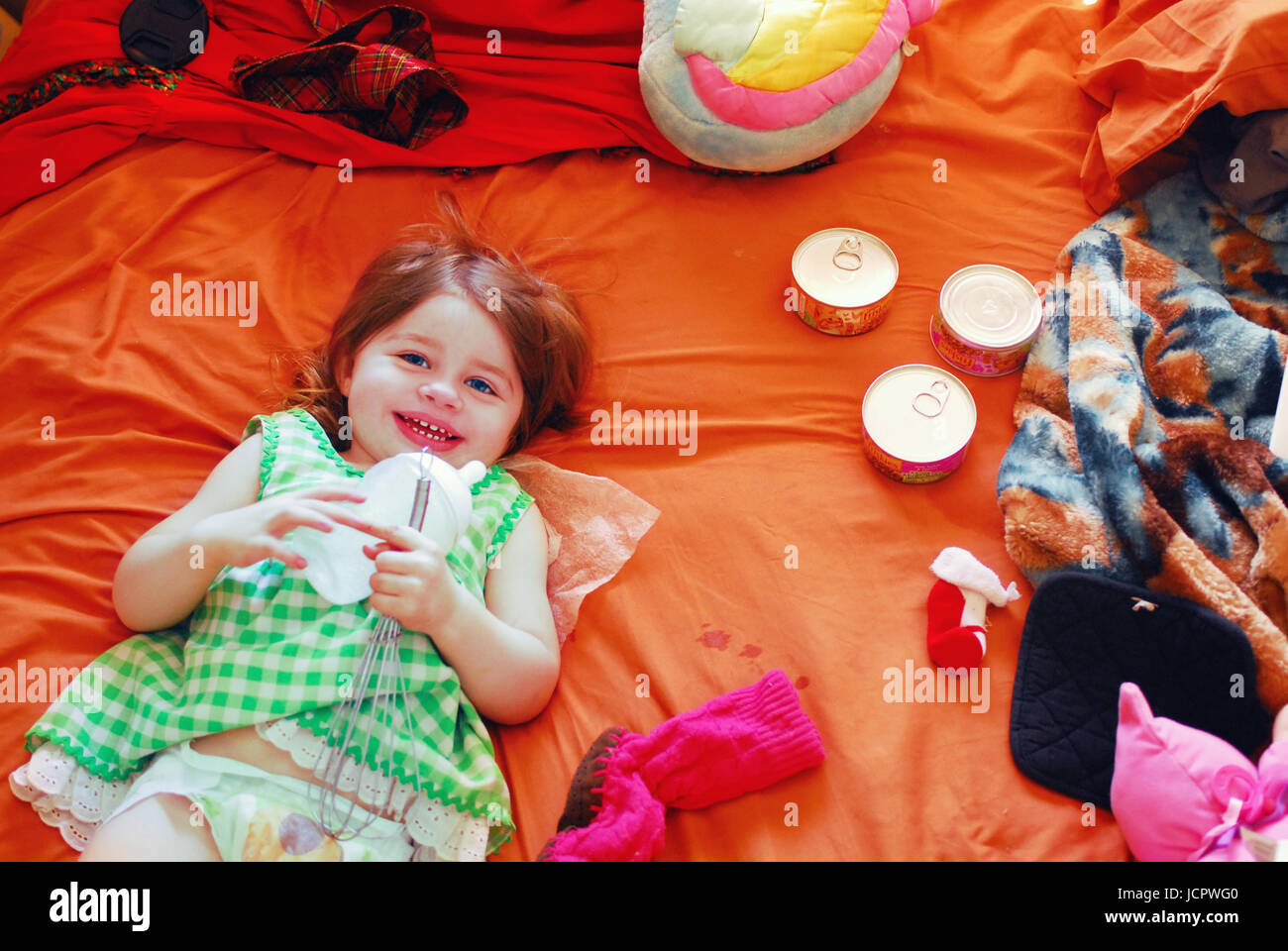 toddler lying on messy bed with assorted objects - Stock Image